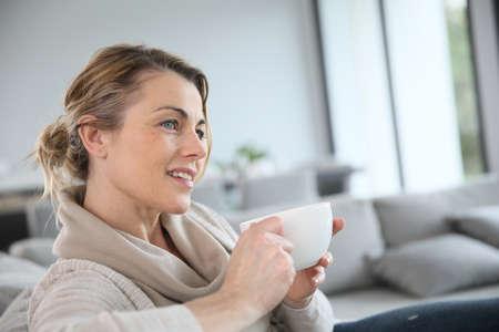 Starší žena v pohovce pití horké kávy