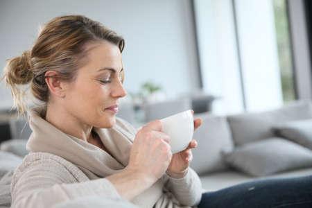 ホット コーヒーを飲むのソファーで成熟した女性 写真素材