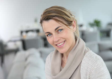 Portrait of middle-aged blond woman at home photo
