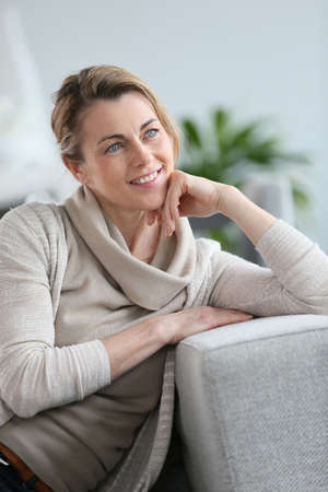 hand on the chin: Portrait of smiling mature woman with hand on chin