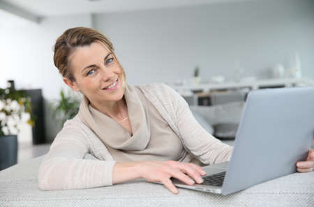 websurfing: Mature woman sitting in sofa an websurfing with laptop Stock Photo