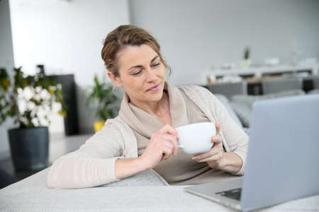 Mature woman relaxing with cup of coffee in front of laptop photo