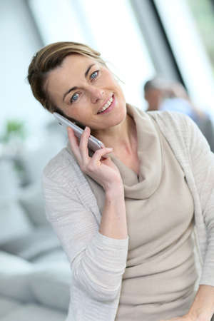 phonecall: Portrait of mature blond woman talking on phone