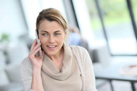 middleaged: Portrait of mature blond woman talking on phone