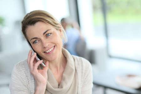 Portrait of mature blond woman talking on phone photo