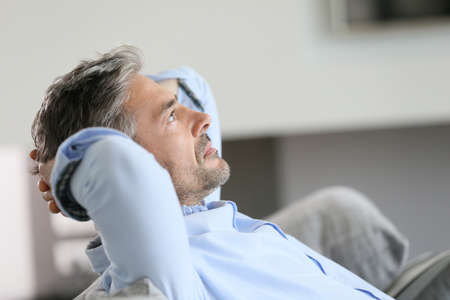restful: Middle-aged man having a restful moment relaxing in sofa