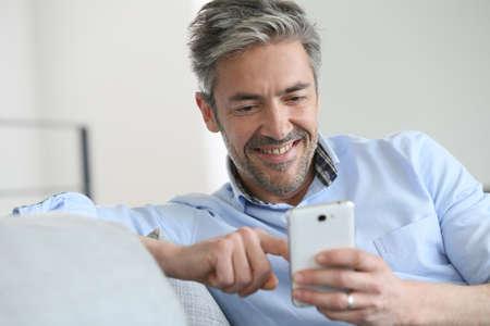 成熟した男のスマート フォンでメッセージを送信します。