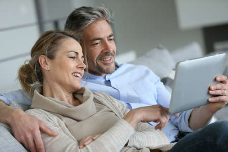 Mature couple relaxing in sofa and using digital tablet 스톡 콘텐츠