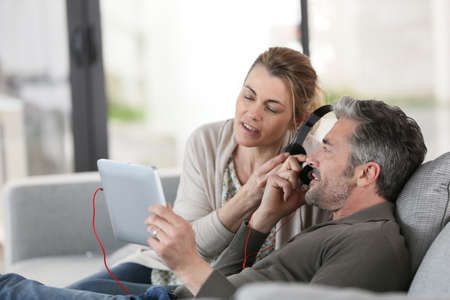 Mature couple at home listening to music with tablet photo