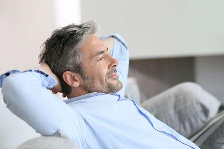 descansando: Hombre de mediana edad que tiene un momento de descanso relajante en sofá