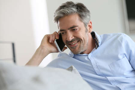 phonecall: Mature man sitting in sofa and talking on phone