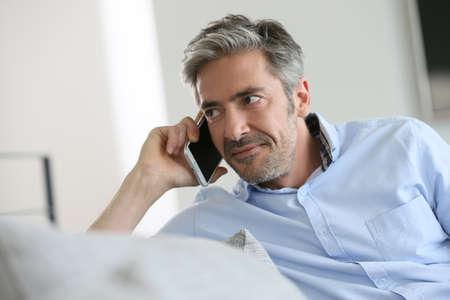 Hombre maduro sentado en el sofá y hablando por teléfono Foto de archivo - 38396768