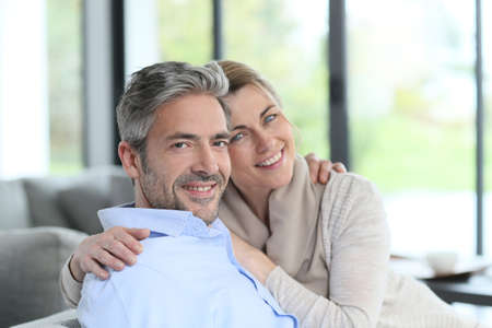 couple on couch: Portrait of mature couple relaxing at home Stock Photo