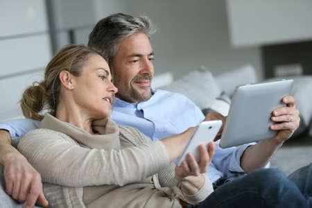 esposas: Pareja madura en casa con smartphone y la tableta