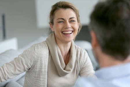 dos personas hablando: Pareja en casa sentado en el sof� y que tiene una charla