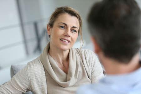 marido y mujer: Pareja en casa sentado en el sofá y que tiene una charla