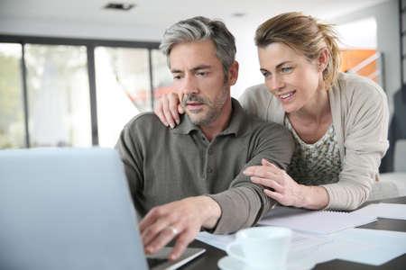 pareja en casa: Pares que calculan el ahorro financiero en internet