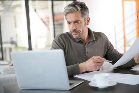 Mature man calculating budget on laptop Stockfoto