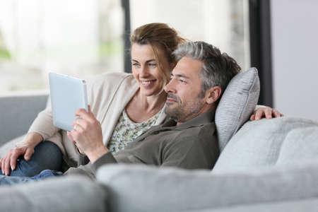 descansando: Pareja madura que usa la tableta digital se relaja en el sof�