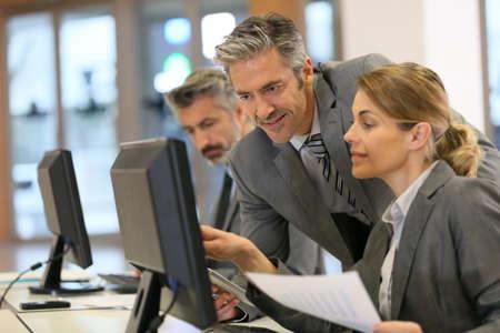 trabajando en computadora: La gente de negocios que trabajan en la oficina en la computadora de escritorio