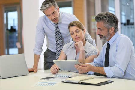 reunion de trabajo: El personal de ventas de reuniones en la oficina, que usa la tableta Foto de archivo