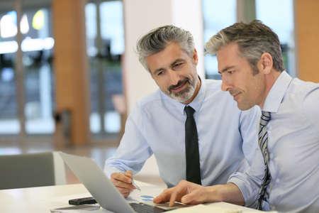 workteam: Businessmen working in office with laptop