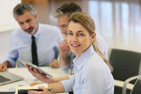attending: Smiling businesswoman attending work meeting