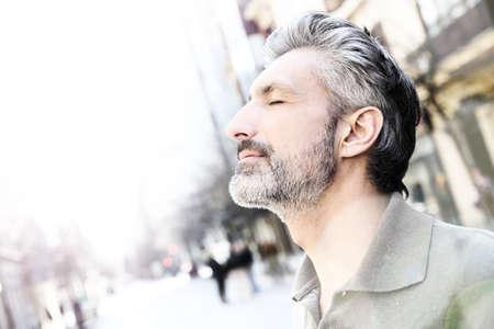 persona respirando: Retrato de hombre maduro sereno en la ciudad