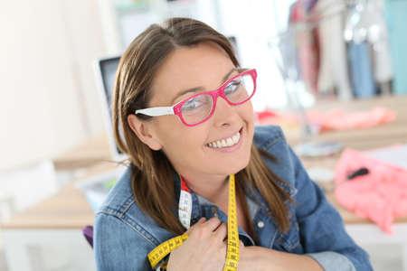 dressmaker: Portrait of cheerful dressmaker in designing studio Stock Photo