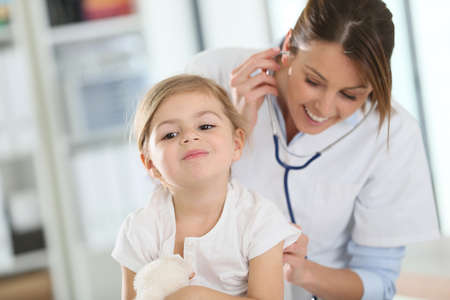 pediatric nurse: Doctor examining little girl with stethoscope