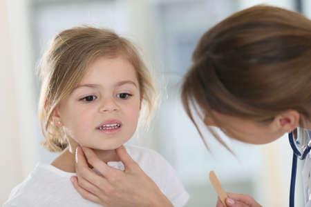 Kinderarts in het kantoor van controle op de keel van het kind