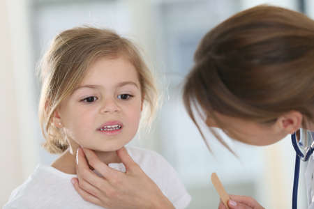 Pediatrician in office checking on child's throat