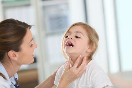 medicalcare: Pediatrician in office checking on childs throat