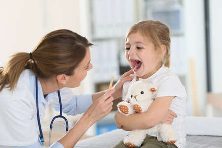 checking: Doctor examining childs throat and mouth