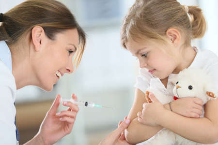 Brave little girl receiving injection in doctors office photo