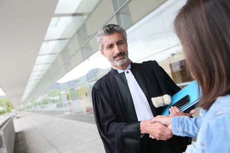 lawyer meeting: Lawyer meeting client in courthouse before trial Stock Photo
