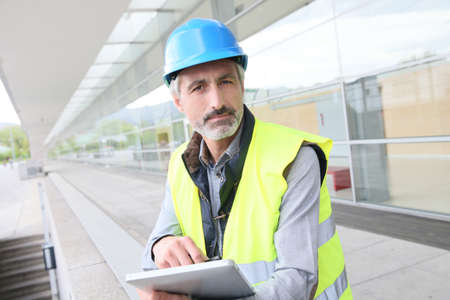 hardwearing: Engineer with hard hat using tablet outside building