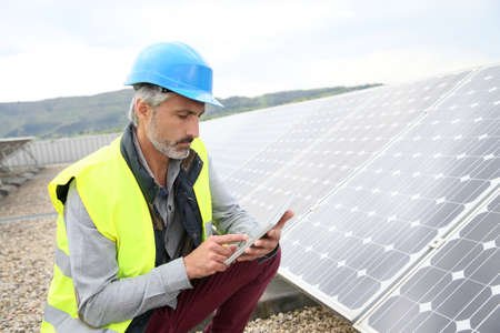 Mature engineer on building roof checking solar panels Stockfoto