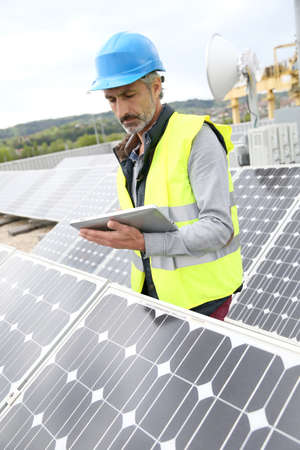 Mature engineer on building roof checking solar panels Stock Photo