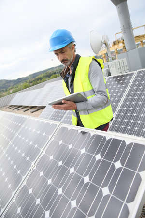 hardwearing: Mature engineer on building roof checking solar panels Stock Photo