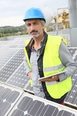 hardwearing: Mature engineer on building roof checking solar panels Stock Photo