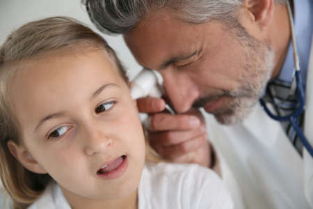 examining: Doctor examining girls ear