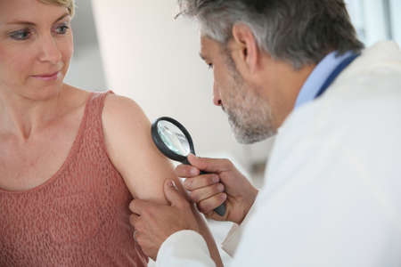 Dermatologist looking at woman's mole with magnifier