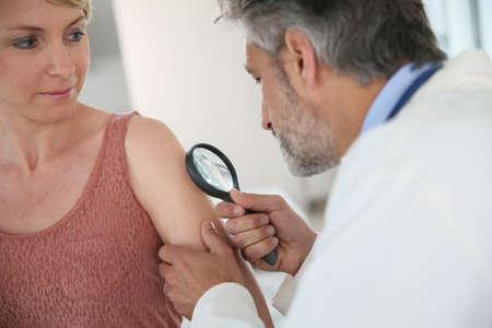 Dermatoloog te kijken naar mol van de vrouw met vergrootglas Stockfoto