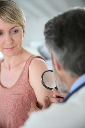 medicalcare: Dermatologist looking at womans mole with magnifier Stock Photo