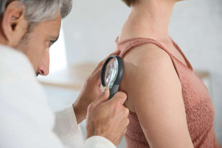 Dermatologist looking at womans mole with magnifier Stock Photo