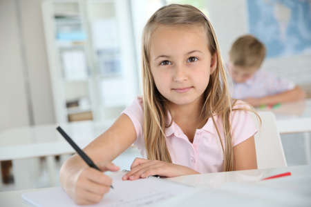 school book: Cute schoolgirl writing on notebook, in classroom Stock Photo