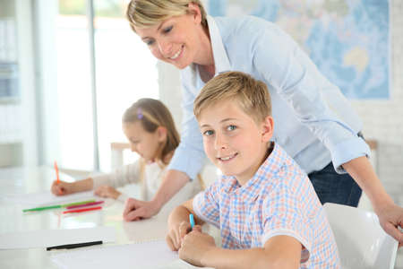 12 class: Teacher helping pupil with writing in class Stock Photo