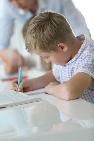 12 class: Schoolboy in classroom writing on notebook