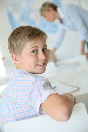 12 class: Young smiling schoolboy in classroom